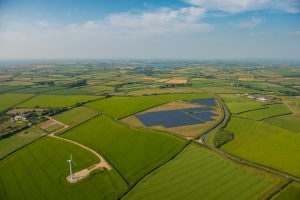 A wind turbine and solar park in a green field